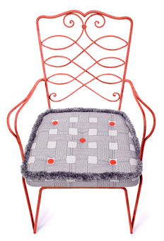 Doug & Gene Meyer outdoor fabric and trim designed for Link Outdoor. Chair cushion in pattern called Crossings with Tweed fringe and Melon canvas buttons.